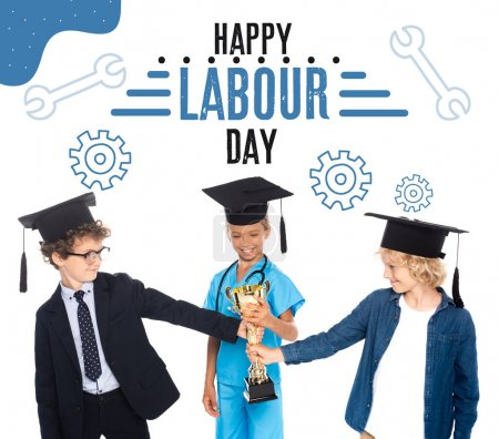 Photo for Kids in graduation caps dressed in costumes of different professions holding golden trophy near happy labour day lettering on white - Royalty Free Image