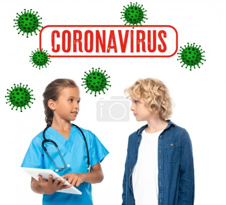 Photo for Kid in costume of doctor using digital tablet near curly boy and coronavirus lettering on white - Royalty Free Image