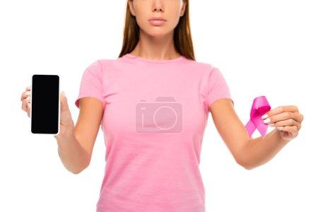 Vue recadrée du smartphone avec écran blanc et ruban de sensibilisation au cancer du sein dans les mains de la femme sur fond flou isolé sur blanc