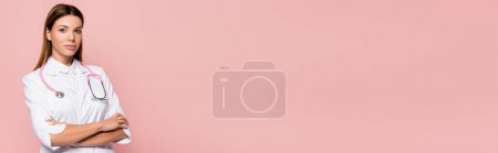 Photo for Young doctor with crossed arms looking at camera isolated on pink, banner - Royalty Free Image