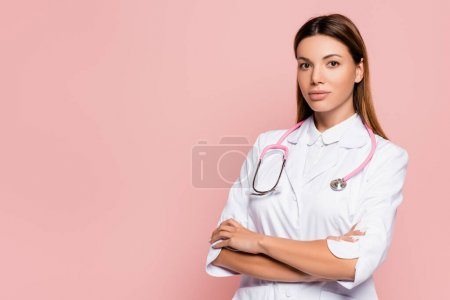 Young doctor in white coat and stethoscope looking at camera isolated on pink