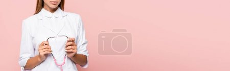 Photo for Cropped view of brunette doctor holding stethoscope isolated on pink, banner - Royalty Free Image