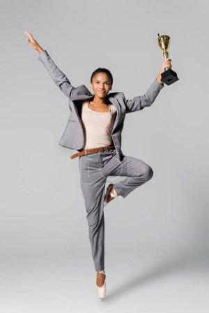 Photo pour Femme d'affaires afro-américaine exécutant un ballet avec tasse dorée isolée sur gris - image libre de droit