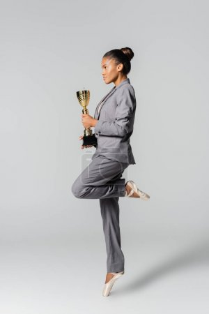 Photo for Side view of african american businesswoman performing ballet with golden cup isolated on grey - Royalty Free Image
