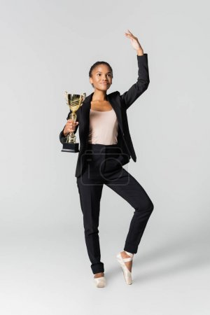 african american businesswoman performing ballet with golden cup isolated on grey