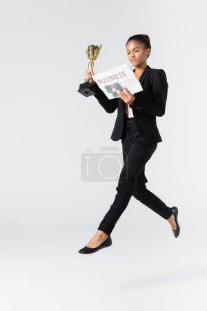 femme d'affaires afro-américaine exécutant un ballet avec journal et gobelet isolé sur gris
