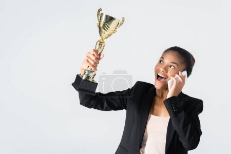 happy african american businesswoman with golden cup talking on smartphone isolated on grey