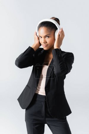 Photo for African american businesswoman listening music in headphones isolated on grey - Royalty Free Image