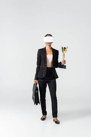african american businesswoman with suitcase and goblet in vr headset isolated on white