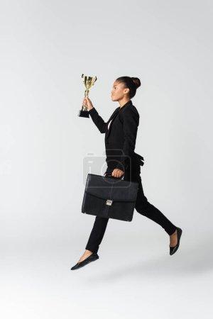 Photo pour Vue latérale d'une femme d'affaires afro-américaine avec valise et gobelet isolés sur blanc - image libre de droit