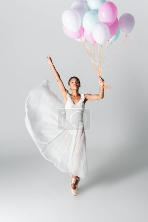 graceful african american ballerina in dress dancing with balloons on white background