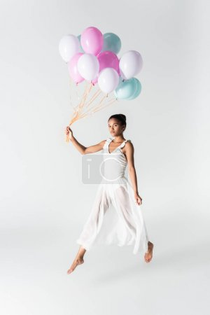 barefoot graceful african american ballerina in dress with balloons on white background