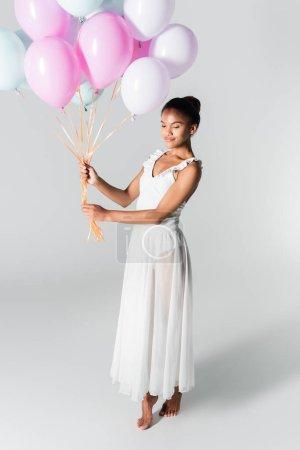 Photo pour Pieds nus gracieuse ballerine afro-américaine en robe avec ballons sur fond blanc - image libre de droit