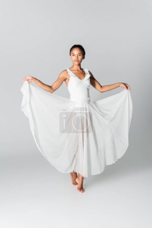 barefoot graceful african american ballerina in dress dancing on white background