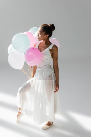 graceful african american ballerina in dress with balloons on white background