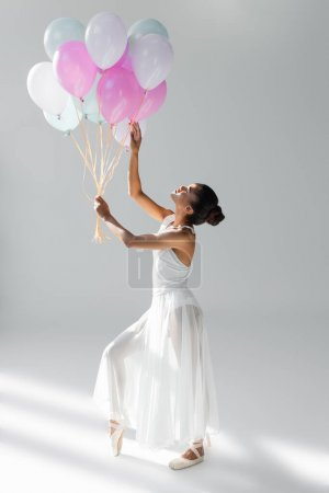 Photo for Graceful african american ballerina in dress with balloons on white background - Royalty Free Image