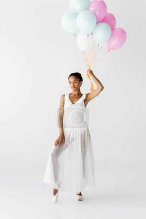 anmutige afrikanisch-amerikanische Ballerina mit Luftballons isoliert auf weiß