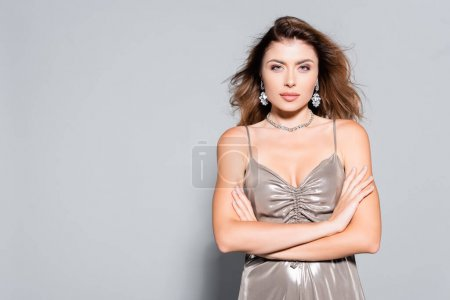 Photo for Elegant woman in dress and jewelry posing isolated on grey - Royalty Free Image