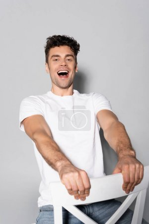 happy young man in white t-shirt on chair isolated on grey