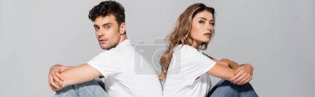 Photo pour Jeune couple en t-shirts et jeans blancs posant dos à dos isolé sur gris, bannière - image libre de droit