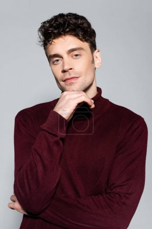 Photo for Young man in burgundy turtleneck jumper posing isolated on grey - Royalty Free Image