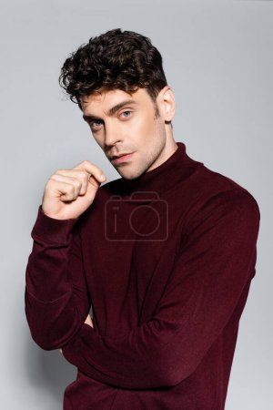 young man in burgundy turtleneck jumper posing isolated on grey
