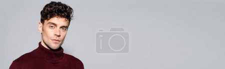 young man in burgundy turtleneck jumper posing isolated on grey, banner