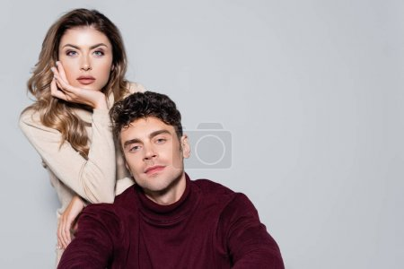 casual young couple in turtleneck jumpers posing isolated on grey