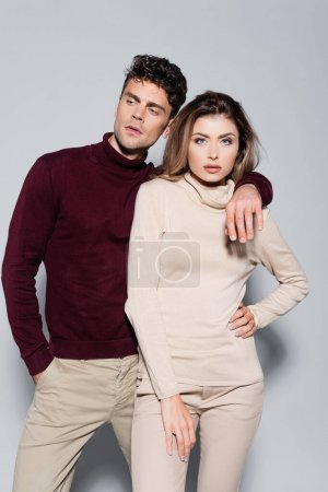 casual young couple in turtleneck jumpers embracing isolated on grey