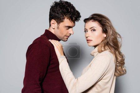 Foto de Vista lateral de pareja joven casual en jerséis de cuello alto aislados en gris - Imagen libre de derechos