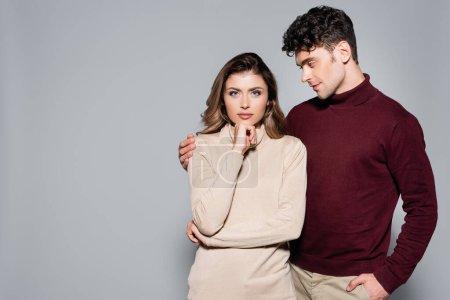 Photo pour Casual jeune couple en pulls posant isolé sur gris - image libre de droit