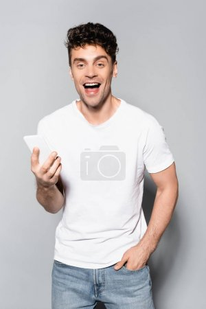 Photo for Happy young man in white t-shirt with smartphone isolated on grey - Royalty Free Image