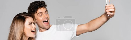 happy casual young couple in white t-shirts taking selfie on smartphone isolated on grey, banner