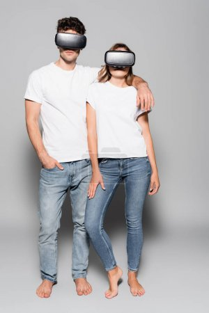 casual young couple in white t-shirts and vr headsets isolated on grey