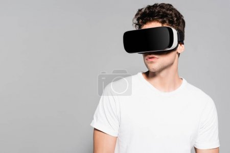 casual young man in white t-shirt and vr headset isolated on grey