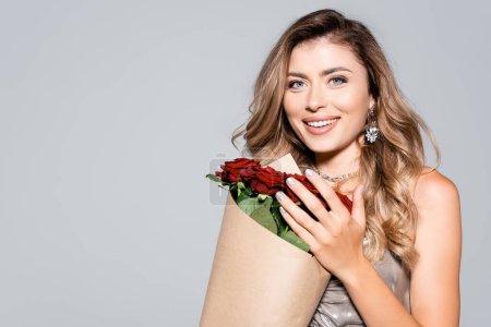 Photo pour Femme élégante et souriante en robe avec bouquet de roses rouges isolées sur gris - image libre de droit