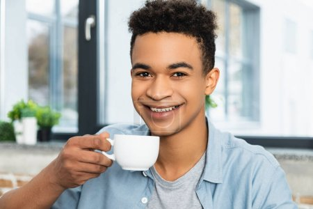 young african american man smiling while holding cup of coffee