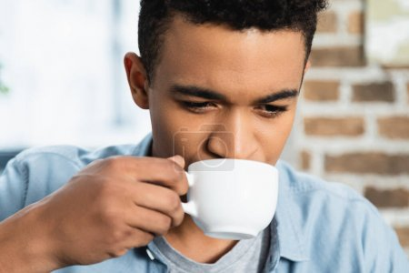 african american man drinking coffee in white cup