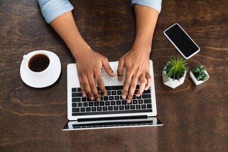 Photo pour Vue partielle de l'homme afro-américain tapant sur ordinateur portable près du smartphone avec écran vierge et tasse de café - image libre de droit
