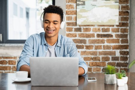 happy african american man in wireless headphone listening podcast near laptop on desk