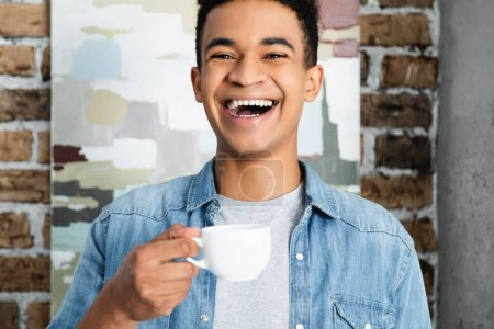 amazed african american man laughing while holding cup of coffee