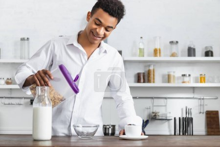 happy african american man holding container with corn flakes near bowl and beverages on table