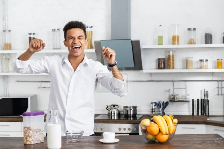 excited african american man standing near table with fruits and beverages