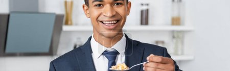 cheerful african american businessman holding spoon with corn flakes, banner