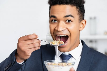 amazed african american businessman eating corn flakes with milk