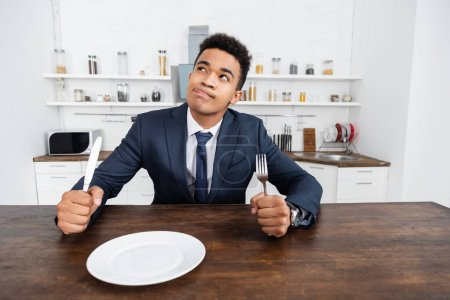 dreamy african american man holding cutlery while thinking and sticking out tongue