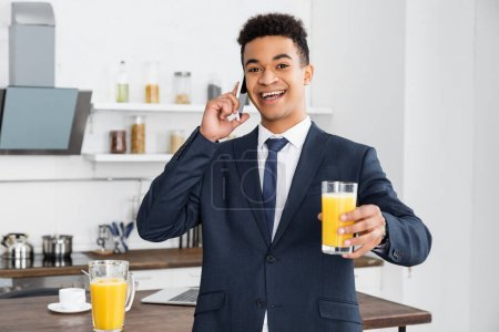 Photo for Happy african american businessman holding glass of orange juice and talking on smartphone - Royalty Free Image