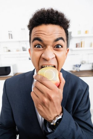 curly african american businessman eating apple at home
