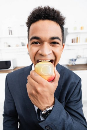 happy african american businessman eating apple