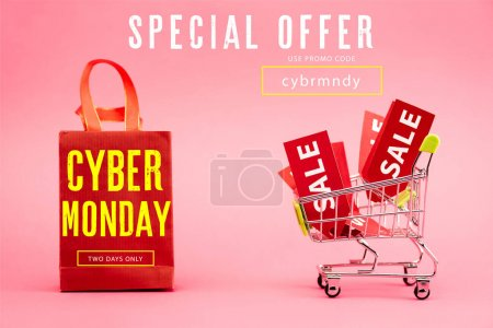 Photo for Red tags with sale in shopping trolley near paper bag with cyber monday lettering on pink - Royalty Free Image